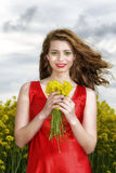 Young  woman in red dress in yellow field Royalty Free Stock Image