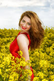 Young  woman in red dress in yellow field Stock Photo