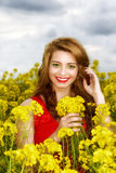 Young  woman in red dress in yellow field Stock Photography