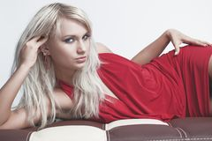 Young woman in red dress. Lying on sofa Royalty Free Stock Photo