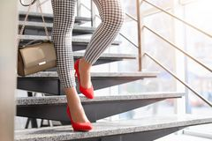 Young woman in red elegant shoes on stairs. Indoors Stock Photography