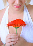 Young Woman with Red Flower. A young woman with a bright red flower, photographed in a studio setting Stock Photo