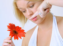 Young Woman with Red Flower. A young woman with a bright red flower, photographed in a studio setting Stock Photography