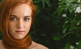 Young woman with red hair around neck as scarf. Beautiful redhead woman with red hair around her neck as scarf, green plants background, copy space stock images