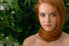 Young woman with red hair around neck as scarf. Natural beauty. Young woman with red hair twisted around her neck, green leaves background with epty space stock photos