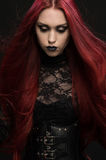 Young woman with red hair in black gothic costume Stock Image