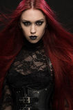 Young woman with red hair in black gothic costume Royalty Free Stock Photography