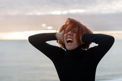 Young woman with red hair clutching her head and loudly screaming from heartache on the background of sea and sunset.  royalty free stock photos