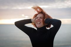 Young woman with red hair clutching at her head writhing in pain on the background of sea and sunset.  stock photography