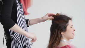 Young woman with red hair cuts hair to woman at the hairdresser stock footage