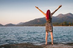 Young woman with red hair is embracing the wonderful nature near the ocean with mountains and forest Stock Photos