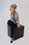 Young woman with red hair. And hat sitting on black cube Royalty Free Stock Image