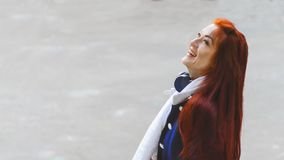 Young woman with red hair with headphones in a blue coat laughs looking up on gray background. Copyspace. royalty free stock photos