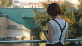 Young woman red hair holding and using mobile phone back view. Redhaired woman calling mobile phone on balcony on background city building. Girl using phone on stock footage