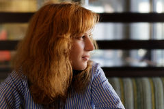 Young woman with the red hair looks away Royalty Free Stock Photos
