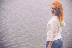 Young Woman with red hair walking outdoor Lifestyle. Concept sea on background film effects colors Stock Photography