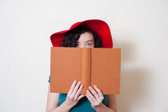 Young woman with red hat reading book face partially covered Stock Image