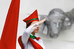 Young woman in red hat standing. Figure of a girl giving a salute during the adoption of the pioneers of the oath on the occasion of the Day of Pioneer Royalty Free Stock Photo
