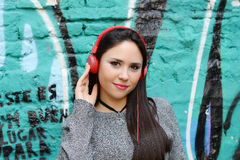 Young woman with red headphones. Outdoors. Stock Photo