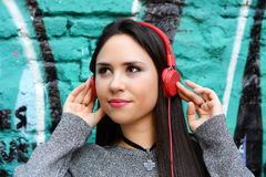 Young woman with red headphones. Outdoors. Stock Image