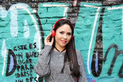 Young woman with red headphones. Outdoors. Royalty Free Stock Photo