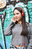 Young woman with red headphones. Outdoors. Royalty Free Stock Image