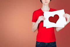 Young woman in red and heart. Woman holds a sign of heart on a red background Stock Images