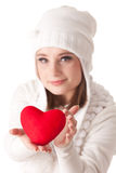 Young woman with red heart in hands. The beautiful young woman holds in hands a red heart on a white background. Selective focus on heart Royalty Free Stock Images