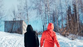 A young woman in a red jacket with her teenage son climbs up the hill and drags along with her tubing. Happy family rides and smiling snowtube on snowy roads stock footage