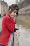 Young woman in red jacket looking depressed Stock Photography