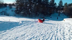 A young woman in a red jacket rolled off a slide on the tubing. Happy family rides and smiling snowtube on snowy roads.slow motion. snow winter landscape stock footage