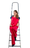 Young woman in  red jumpsuit on  ladder Royalty Free Stock Photography
