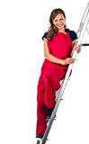 Young woman in a red jumpsuit on  ladder Stock Photos