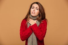 Young woman in red knitted sweater with angina symptoms holding. Her neck, looking at camera,  on beige background Stock Photos