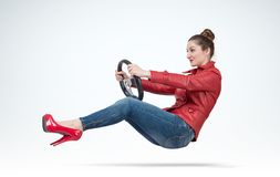 Young woman in red leather jacket with car steering wheel, auto concept. Royalty Free Stock Photography