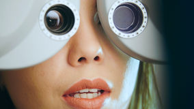 Young woman with red lips checks the eyes on the modern equipment in the medical center Stock Image