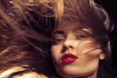 Young woman with red lips and flowing hair Stock Photos