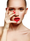 Young woman with red lips and red nails, touching her face Royalty Free Stock Images
