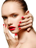 Young woman with red lips and red nails, touching her face Stock Photography