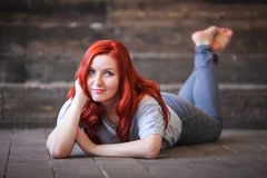 Young woman with red long hair indoor portrait lies on wooden floor stock images