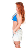 Young woman with red long hairs posing in bikini and jeans shorts Royalty Free Stock Image