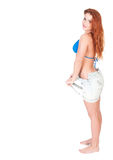 Young woman with red long hairs posing in bikini and jeans shorts Royalty Free Stock Photos