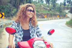 Young woman on a red motorbike on the road Stock Image