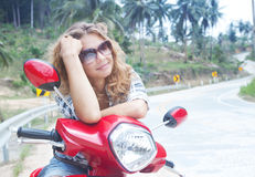 young woman on a red motorbike on the road Royalty Free Stock Images