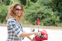 Young woman on a red motorbike on the road Royalty Free Stock Photos