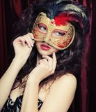 Young woman in a red mysterious  mask Stock Image