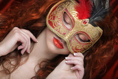 Young woman in a red mysterious  mask Stock Images