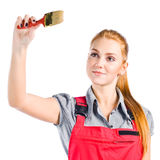 Young woman in red overalls with brush Royalty Free Stock Photo