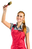 Young woman in red overalls with brush Stock Photo
