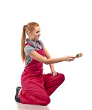 Young woman in red overalls with brush Royalty Free Stock Photography
